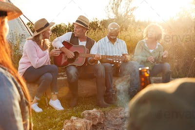 Group Of Mature Friends Sitting Around Fire As They Drink And Sing Songs At Outdoor Campsite