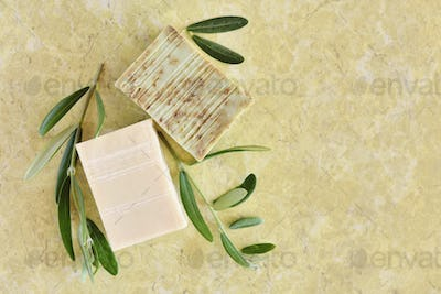 Handmade soap bars and olive branches on color background, top v