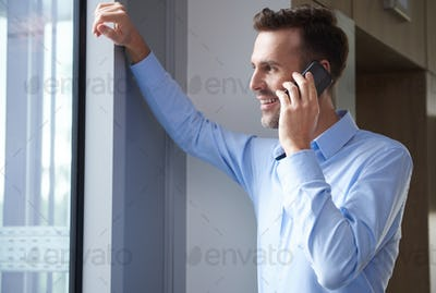Leaning on window and talking on the phone