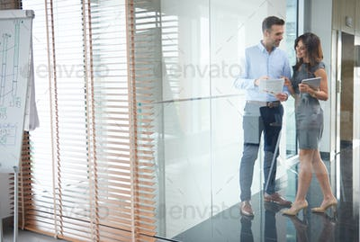 Business partners behind glass wall