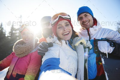 Group of four happy snowboarders