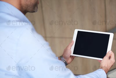 Digital tablet held by business person