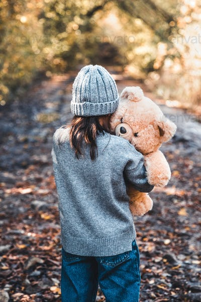 Little girl hugs her bear on a background of nature, autumn, durba
