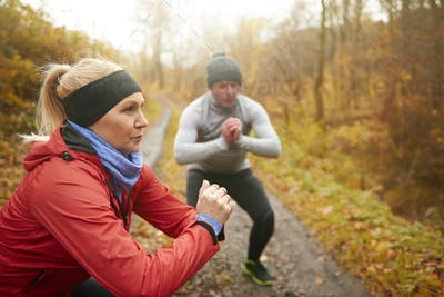 Athletic couple doing squats among forest