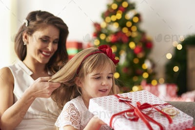 Mother is combing girls hair