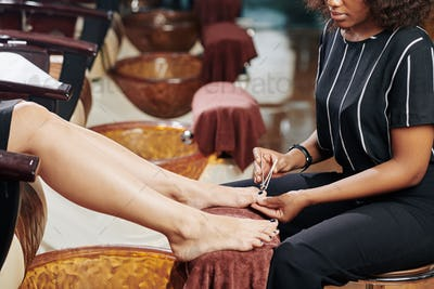 Woman giving client pedicure