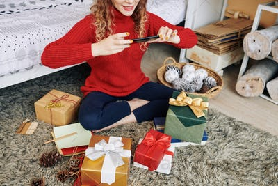 Positive woman photographing presents