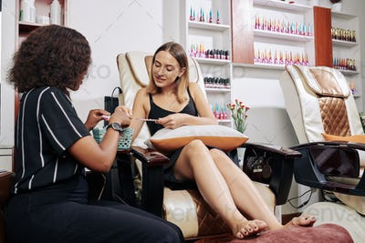 Manicurist helping client to choose nail polish