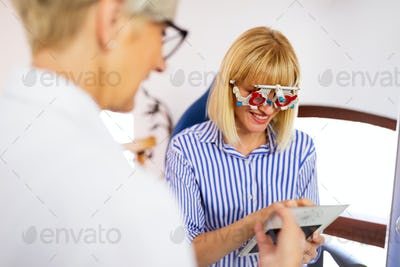 Young woman taking an eyesight test examination at an optician clinic