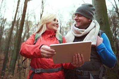 Low angle view of couple with digital tablet