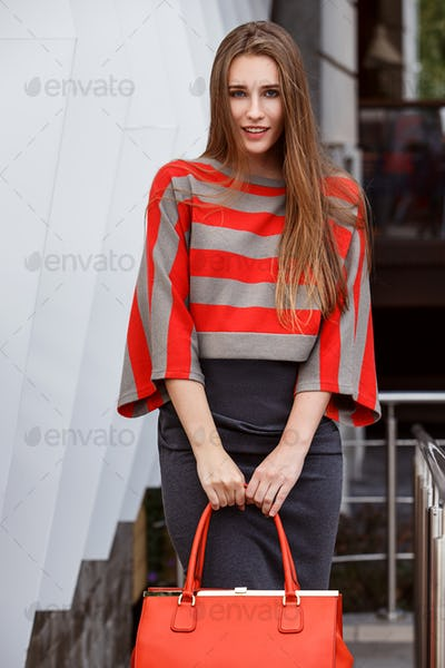 Fashionable girl dressed in a gray skirt, a striped red and gray blouse holding a red bag poses in