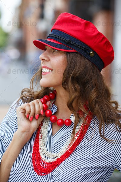 Stylish brunette girl dressed in a striped blouse, red beads and a red cap poses in the city street