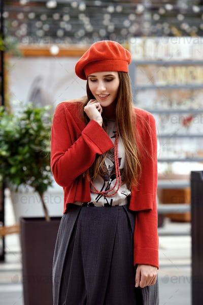 Fashionable girl dressed in a gray skirt, a red blouse on the t-shirt and red beret poses in the