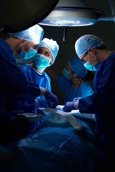 Team of surgeons making important operation