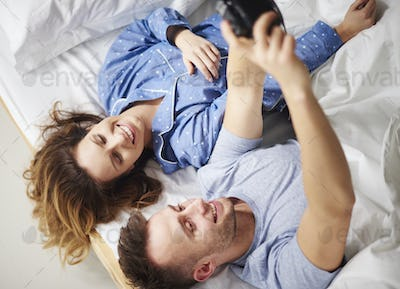 High angle view of couple with camera on bed