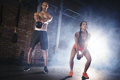Fit couple practicing with kettlebell