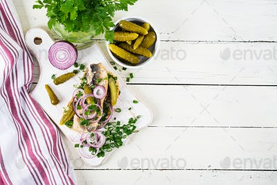Traditional Dutch sandwich with herring and pickles cucumbers on white table. Smorrebrod.Top view