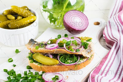 Traditional Dutch sandwich with herring and pickles cucumbers on white table. Smorrebrod.