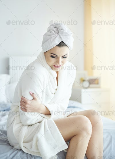 Woman holding her belly in bedroom