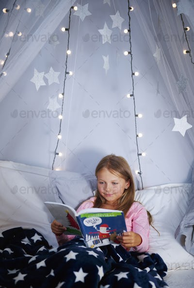 Girl reading a book on bed