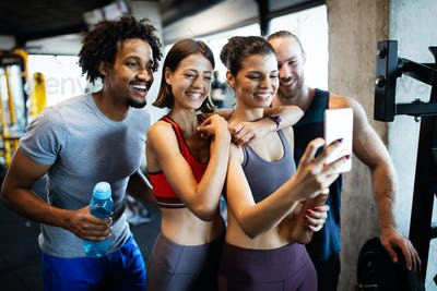 Group of friends having fun at the gym, making a selfie