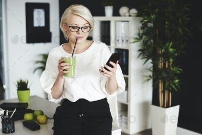 Woman drinking vegetable juice and using mobilephone