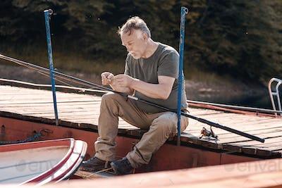 Senior man preparing his fishing rod