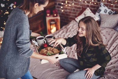 Girl sharing cookies and mulled wine with her friend
