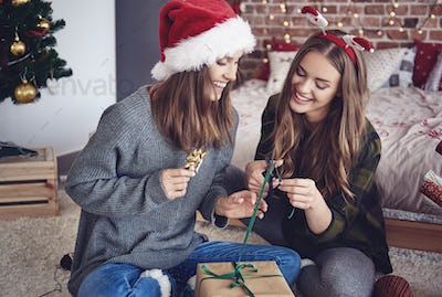 Sisters packing gifts in bedroom