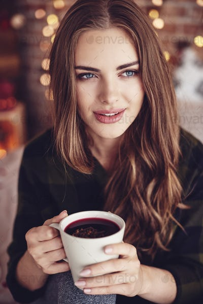 Beautiful woman holding a mug of mulled wine with ginger