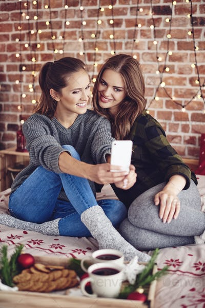 Two best friends taking selfie in bedroom