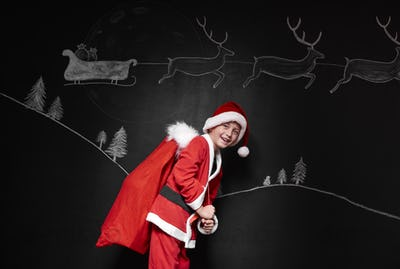 Boy in santa claus costume carrying a sack of gifts