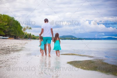 Father and his two little daughters walking by the sea