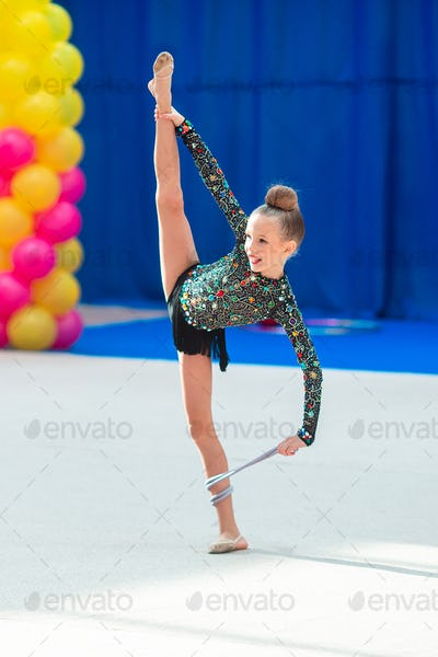 Beautiful little gymnast girl on the carpet on the competition