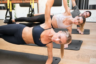 Suspended elbow side plank Trx exercises in a gym