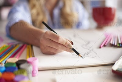 Woman drawing sketches in the book