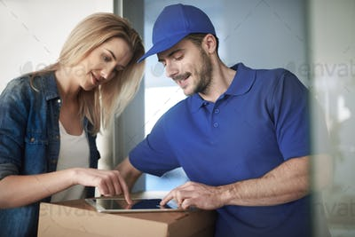 Woman signing package by using digital tablet