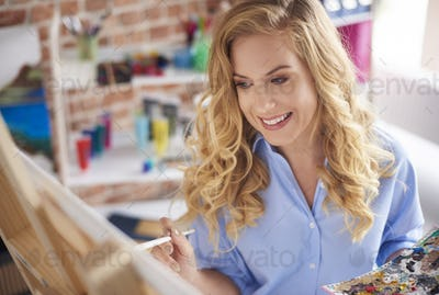 Woman is smiling while creating image