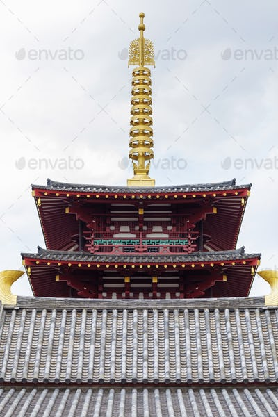 Top of pagoda tower on light background with clouds