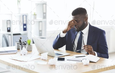 Tired afro businessman taking his glasses off, touching nose bridge