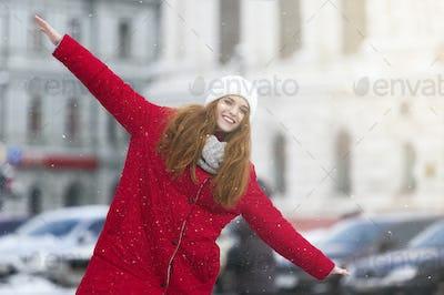 Positive young girl having fun on winter street