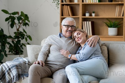 Cheerful middle aged woman in casualwear bending to her senior father shoulder
