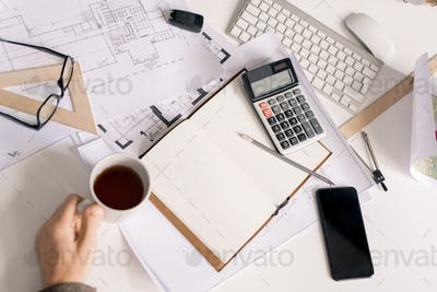Overview of hand of engineer with cup of black tea or coffee by desk during work