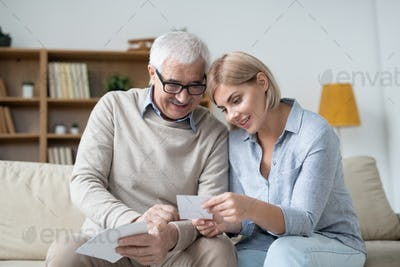 Pretty woman holding photo of her family while showing it to senior father