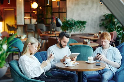 Blonde girl and two guys sitting in armchairs in cafe and scrolling in gadgets