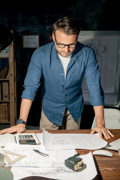 Mature engineer in casualwear looking at sketch on paper while working overtime