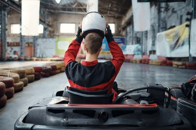 Kart racer puts on helmet, back view