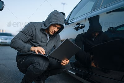 Car thief with laptop hacking alarm system