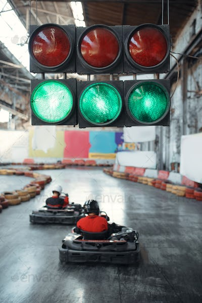 Two kart racers starts race, green traffic light