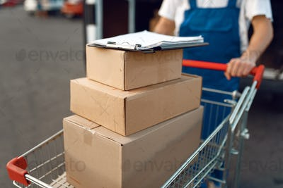 Deliveryman holds cart with stack of boxes